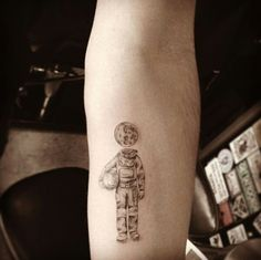 small astronaut moon forearm tattoo