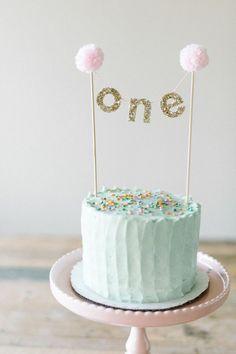 idée pour une décoration anniversaire originale en pom pom et guirlandes glitter, gateau anniversaire 1 an fille au glaçage pastel
