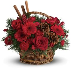 The scents of the season! Christmas greens, bold red flowers and cinnamon sticks make this a fragrant floral arrangement for Christmas gatherings.