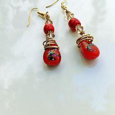 Fiamma: são brincos de 5 cm de comprimento (sem o anzol) com pequenas e brilhantes gotas vermelhas, cristais swarovski em champanhe-dourado e fio de bronze.