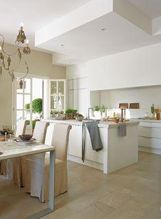 La encimera, de piedra natural. Cocina blanca con isla central y office con sillas con fundas