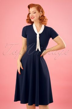 Feminine and flirty this 50s Lillie Swing Dress in Navy and Ivory!Wow, what a stunner! This vintage inspired beauty features an elegant V-neckline with a contrasting tie neck and flattering short sleeves. The combination of the semi-swing style skirt and the fitted top creates a super feminine fifties silhouette. Made of a supple, stretchy, crêpe-like fabric in navy blue that wears beautifully. This dress is sure to win your heart and not just yours... ;-)Semi-swing styleV-necklineTie…