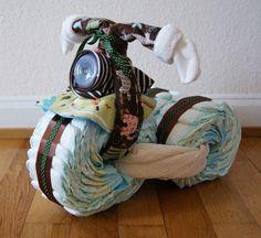 """Hast du schon Mal eine Idee für ein Babygeschenk gesucht? Am liebsten nicht bloß irgendein Kuscheltier, sondern etwas nützliches? Der US-Amerikanischer Trend von Windeltorten wird erweitert, und man kann sehr kreativ damit werden, z.B. einen Motorrad basteln! Es gibt bei YouTube mehrere DIY Videos, gib z.B. """"diaper motorcycle"""" ein, und dort lernt man den Aufbau Schritt-für-Schritt. Ich habe ein Dreirad daraus gemacht für Stabilität und weil ich es auch schöner finde, aber die Kreati..."""