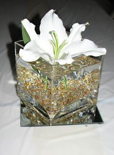 centerpieces on tables - filled with water, gold marbles and lily