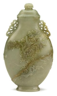 Chinese celadon jade ovoid covered vase     18th/19th century     The flattened ovoid vase with scroll handles at shoulder, carved to face with magpies among plum blossoms, surmounted by a tiered cover with pierced finial, and raised on flaring footring.     H: 10 1/4 in.
