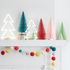 Go for holiday décor that's as bright and bold as you are—so unexpected and fun. A few standout pieces to pull it off: neon tree lamps and retro bottle brush trees.