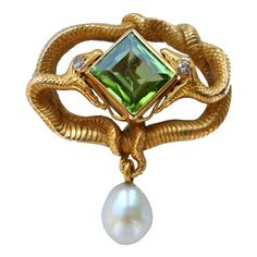 KARL ROTHMÜLLER An Eternal Entwined Snakes Brooch  Germany  circa 1900  The naturalistic snakes biting a large emerald cut fine green peridot.
