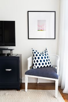 This sunny corner is the perfect little reading nook. Next to this is Natasha's favourite DIY, a refurbished buffet which she converted into a media console. Artwork is by Emily Jeffords.
