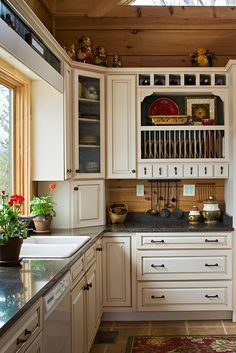 Light painted cabinets with dark counter tops & warm wood tone walls.