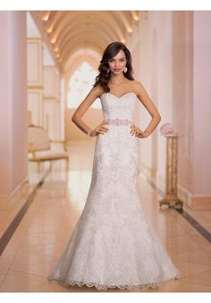 Long, narrow and oh-so slim-fitting, this sheath wedding dress with hand placed elegant Lace over Dolce Satin from the Stella York collection is the epitome of sexy. You'll love how the hand beaded Diamante embellishments sparkle under soft light. Additional details include a lovely sweetheart neckline, scalloped lace hem, sparkly beaded belt, traditional court train, and a zipper back hidden under sparkling crystal buttons.  The Knot provides price estimates to give you a general idea of…