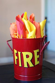 Firefighter Party Decoration...wrap your plastic ware in red, orange and yellow napkins and put in bucket for flames