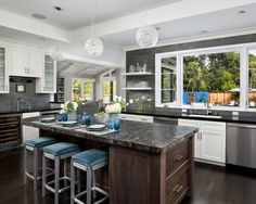 This spacious kitchen offers a chic coastal vibe with its ocean blue pops of color and sunny view of the outdoor patio. White cabinets provide a beautiful contrast to the gray tile backsplash, while a dark brown island with a black granite countertop offers extra space for casual dining.