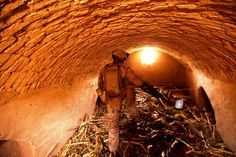 Corporal Jesse Kelley from Denver, combat engineer, 1st Squad, 1st Platoon, Charlie Company, 1st Combat Engineer Battalion, searches for improvised explosive devices in dried poppy kept in an underground storage compound during Operation Speargun in Urmuz, Afghanistan, March 28, 2012.