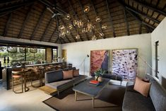 Designed for Megan Ralph Spaces for a safari guest lodge, these beautiful bronze ceramic wall tiles create a striking talking point at the bar of this establishment whilst beautifully complimenting the rest of the interior design.  #ceramic #wallpaper #design #interiordesign #architecture #southafrican #guesthouse #safari #decor #fireplace #tiles #wall #walltiles #featurewall #designideas #designinspo #homerenovations #hotel #renovations #bar