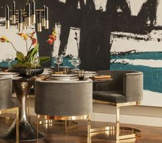 Chic dining room features large teal and black abstract art framing black and gold art deco chandelier over black and gold dining table surrounded by gray barrel back dining chairs over wood herringbone floor.