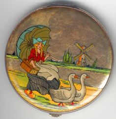 Gorgeous foil GWENDA compact depicting a Dutch girl herding her geese along the edge of a canal with a windmill in the background.