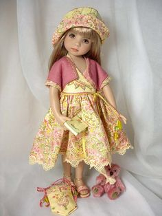 Pretty doll dressed in pale pink and yellow spring frock and hat