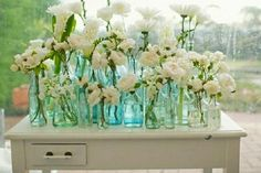 Another way to display a mixture of bottles is in a drawer or on top of a vintage desk or dresser. The bottles can either be mixed and matched, or be all the same style. You can also vary the style with the piece of furniture you display them from, as well as the variety of flowers you choose.