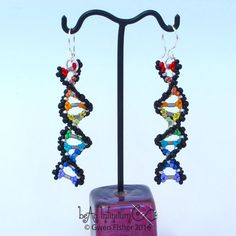For the molecular biologist in you...  These lacy beaded earrings use a variety of glass seed beads and bugle beads, all woven together to resemble a double helix of DNA. Bugle bead rungs separate the colored base pairs of molecules. The colors include every color in the rainbow, plus silver and black.  The helix is stiff yet the beadwork is still quite flexible. The ear wires are sterling silver. These are long earrings that are light for their size. Earrings are are 15 mm (half inch) wide…