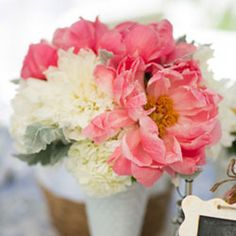 Table arrangement composed of coral peonies, white dahlias, white hydrangea, and dusty miller. Created by April Peet of April Flowers