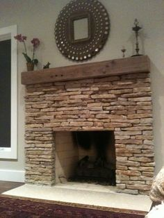 stacked stone fireplace with rustic wood mantle. would have less space between mantle and opening though.