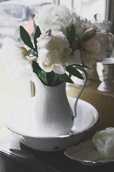 Enamel bowl and pitcher filled with fresh flowers.