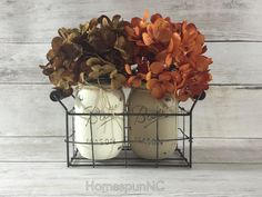 HomespunNC's Mason Jar Wire Baskets add the perfect touch of rustic chic décor to your home or office! These Mason Jar Wire Baskets can be placed in any room of your home or office perched on a mantel or used as a centerpiece/table décor. This Mason Jar Wire Basket measures approximately 9 long x 3.75 wide x 5.5 tall.  Pictured in this listing:  1 distressed Burlap & 1 distressed Vanilla Mason Jars with Orange & Brown Hydrangeas (Pic 1)  2 distressed Burlap Mason Jars with Purple Hydrangeas…