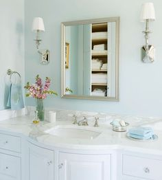 Dream Bath in Blue: A silver-frame vanity mirror -- disguising a handy medicine cabinet -- complements the finish of the faucet and other hardware throughout the room. One drawer in each vanity has an electrical outlet built in, so the hair dryer or curling iron are never left out on the counter.  Ingenious idea.