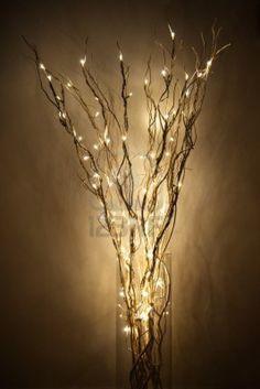 lámpara hecha de braches con luz LED en un frasco de vidrio cerca de una pared Foto de archivo
