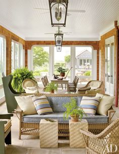 A porch's antique wicker sofa is topped with striped pillows in a Groundworks fabric.