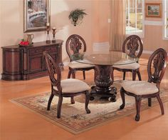 Awesome pedestal round glass dining table with large rug and wooden flooring.