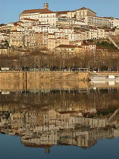 The historical city of Coimbra, Portugal. Reflected in the Mondego River. Visit Portugal, Portugal Travel, Spain And Portugal, Places To Travel, Places To Go, Coimbra Portugal, Iberian Peninsula, Beautiful Places To Visit, Amazing Places