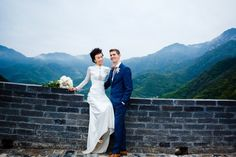 Bride Emily wearing the long sleeve bamboo lace Wallis wedding gown from the Wallis in Love Collection for her unique wedding at the Great Wall of China.