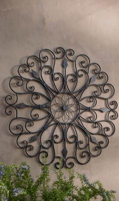 Inspired by the ornamental ironwork of the New Orleans' Garden District, our Gracie Iron Wall Art boasts scrolled iron details that create playful negative spaces with a central flower medallion.