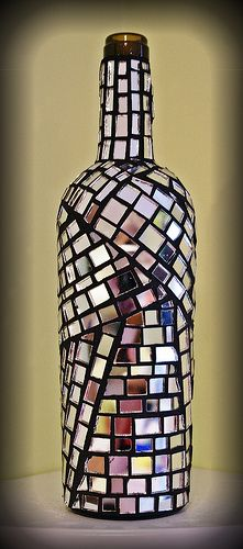Recycled wine bottle using mirror glass and charcoal grout. Looks very cool in the sunlight with the light reflecting all around.