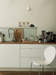 applad white slab kitchen, butcherblock, glass backsplash