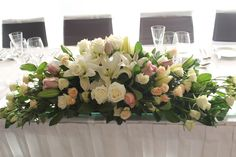 Bridal table floral arrangement of fresh roses and Lisianthus.