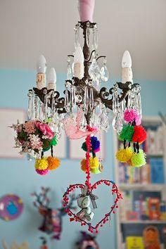 Pompons coloridos, flores artificiais e até um bonequinho de pano, dentro de um coração de arame envolto por bolinhas de lã, mudam totalmente o visual do lustre do quarto de Bertha, filha do designer Marcelo Rosenbaum