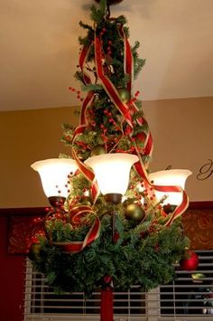 Use a plain wreath upside down. Bend the branches to attach to the light. Wrap a matching garland around the light making sure to hide the wire backing on the wreath.  Needs about 2 sets of garland to look full. Then decorate however you like. Super easy!