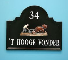 Shaped Top House Sign in black with hand painted white letters and ploughman motif.  Sent to the Netherlands.  www.rockartisansigns.co.uk