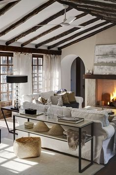 Cottage Living Room with High ceiling, Ceiling fan, Neutral area rug, Cement fireplace, Exposed beam, Hardwood floors