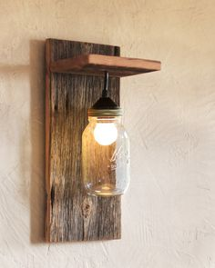 "This mason jar light fixture is the perfect wall sconce for rustic, country, or western décor. Made from reclaimed barn wood, it looks great with or without the rope detail. Hang one on either side of the bed or bring a rustic touch to your living room.  ROPE ACCENT OPTIONAL This sconce is available with or without the rope accent. Please select which variation you want when purchasing.  SIZE The finished product is 7.25"" wide x 16.5"" high x 6.5"" deep.  LIGHT BULB & INSTALLATION This fixture…"