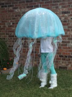 Kate as a jellyfish. Use a clear umbrella, cover with bubble wrap (got mine at UPS store), cover that with turquoise tulle. Then add mini battery powered lights (ordered off of Amazon). #jellyfishcostume #jellyfish #halloweencostume #halloween