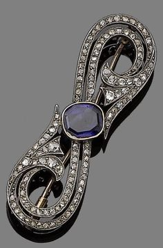 An Edwardian sapphire and diamond brooch, early 20th century. The curved openwork brooch, set to the centre with a cut-cornered step-cut sapphire, and throughout with rose-cut diamonds, mounted in silver and gold, length 4.8cm.