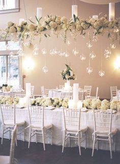 Centros de mesa colgantes con velas, flores y esferas de cristal.