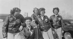 Susie Winston Bain (2nd from right) poses with four fellow WASPs by a car, circa 1944. The women wear the early WASP trainee uniform of a white blouse, khaki trousers, and A-2 leather jacket with Fifinella patch ~