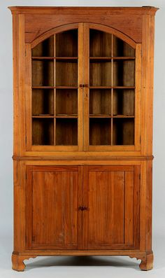 """East Tennessee cherry corner cupboard with arched doors, Greene County. One piece cupboard with ogee cornice and canted returns over arched sixteen pane doors, medial ogee molding over two doors, ogee base molding transitioning to ogee bracket feet. 91 1/2"""" H x 52 1/4"""" W x 28 1/4"""" D. Circa 1820."""