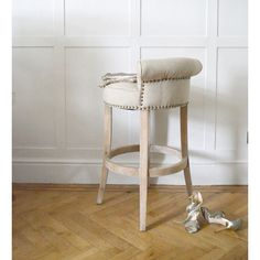 We love this gorgeous barstool! Beautiful in beige linen fabric and complete with elegant aged brass studding that continues round the back. With stunning distressed legs this stool is a sleek, sophisticated work of art. It would look fabulous next to natural tones around a kitchen island or in front of an ultra-modern, trendy bar.