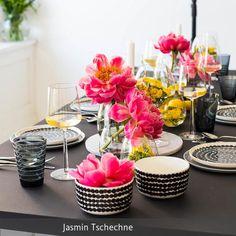 Schwarz-weiße Tischdekoration mit tollen Farbakzenten in Pink und Gelb. Zarte Trommelstöckchen sind eine schöne Ergänzung für die großen Blüten. Mehr Ideen auf roomido.com