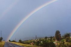 The end of a rainbow hits three figures at the end of a rural road. by Holly Clark - Sky, Rainbow - Stocksy United Late Summer, Summer Days, Under The Rainbow, Kwazulu Natal, Blue Rain, South Africa, The Unit, Sky, Stock Photos